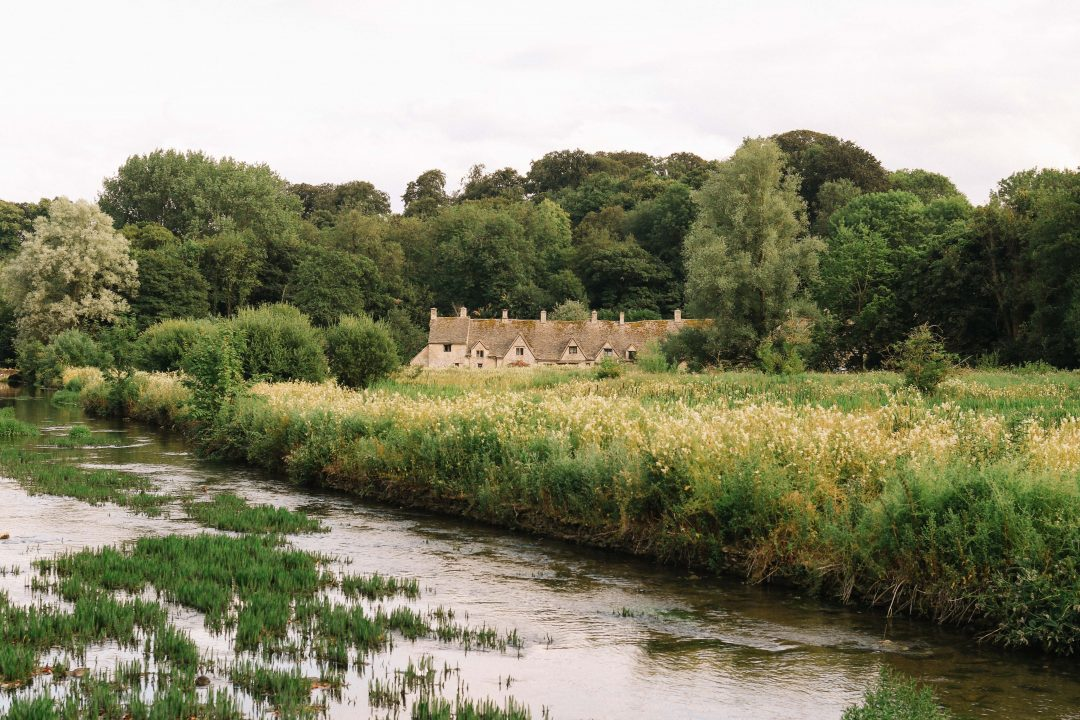 The row of cottages known as Arlington Row in Bibury, hidden behind a water meadow.