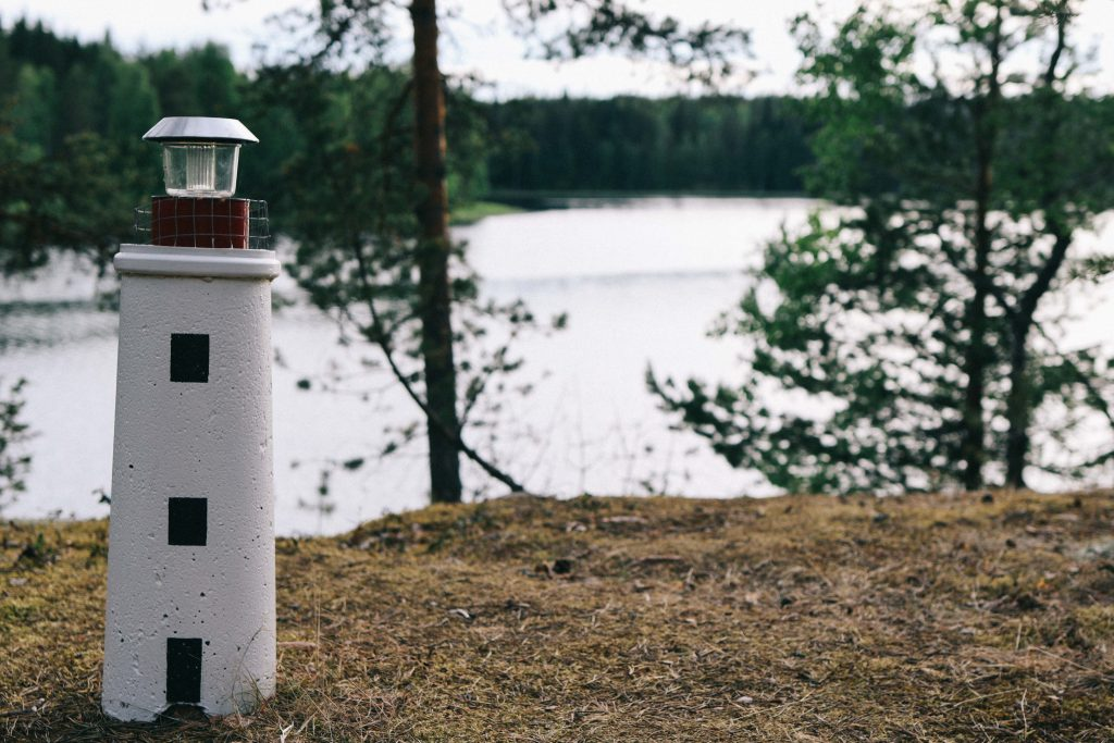 A small statue of a lighthouse overlooking a Finnish lake in Tampere.
