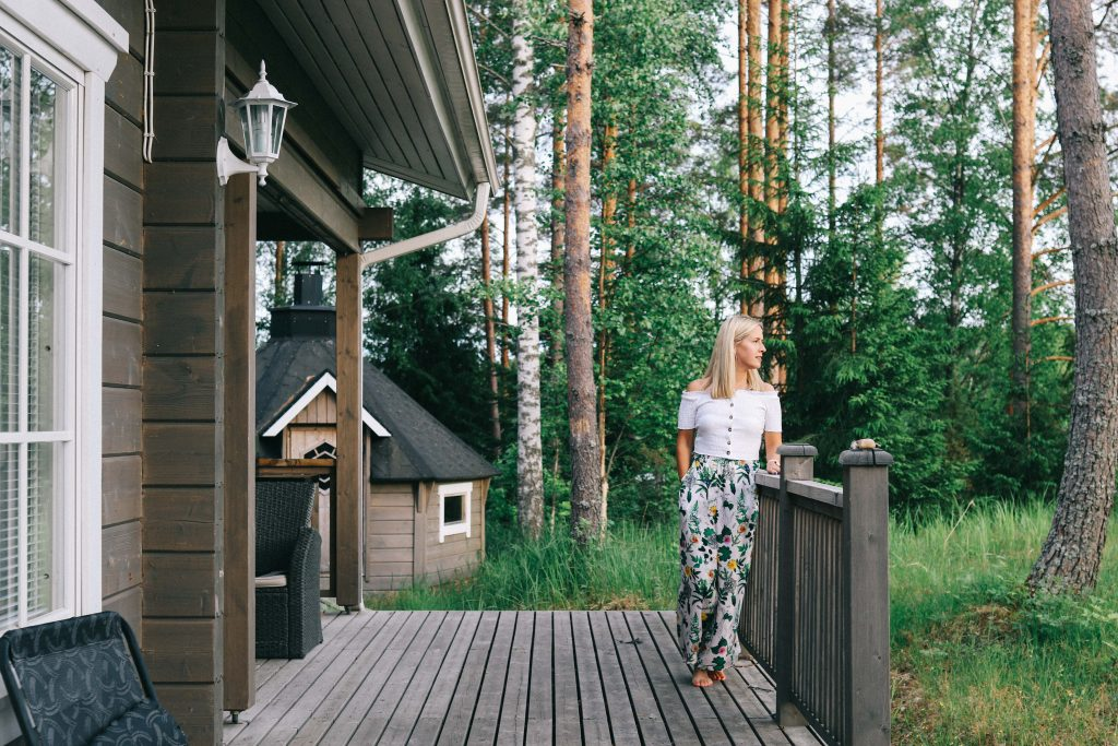 A girl stood on the veranda of a log cabin, in a woodland in Tampere.