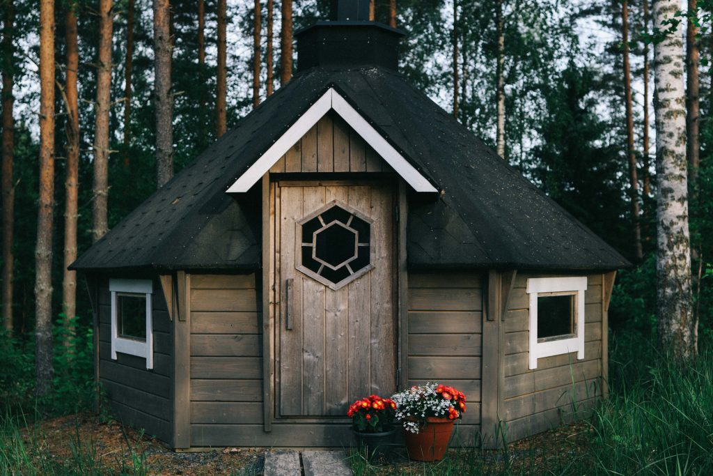 A small log cabin in the middle of the woods in Tampere. Has a small chimney and white windows.