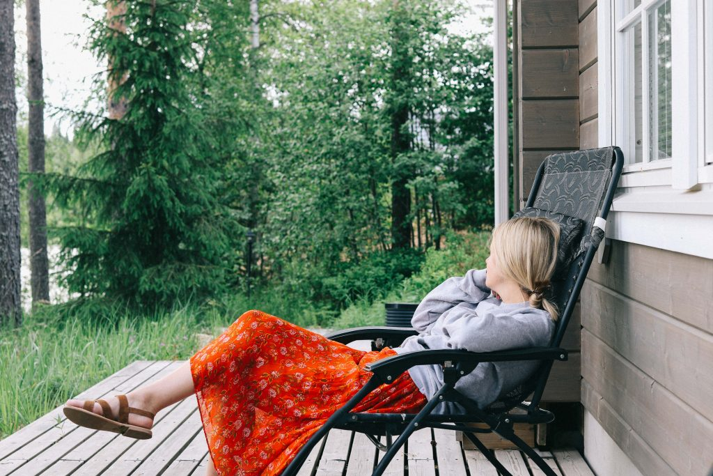A girl reclining in a chair on the deck of a log cabin in Tampere.