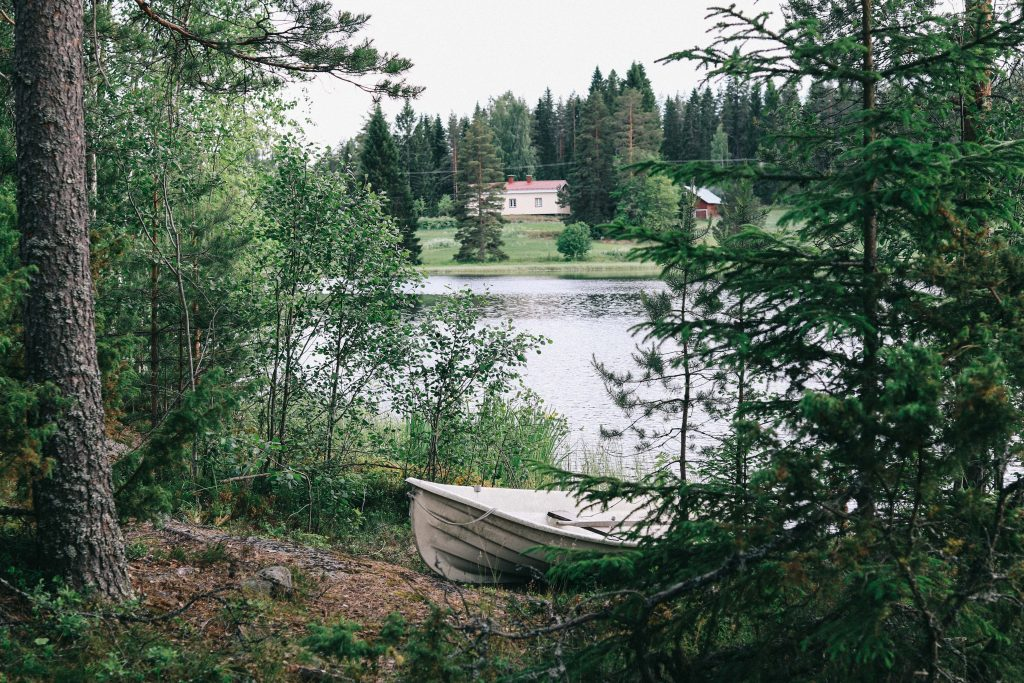 A small white boat pulled ashore one of the Finnish lakes in Tampere.