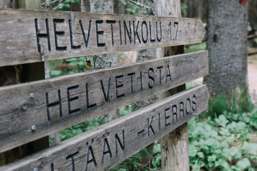 A wooden sign showing the way to Helvetinjärvi National Park.