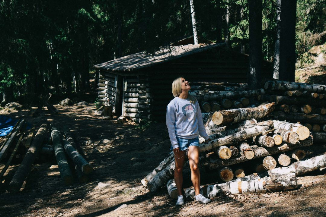 A girl stood in a forest in Tampere, surrounded by chopped woods and a small log cabin.