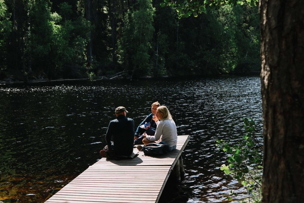 A group of three hikers have lunch on a jetty overlooking a lake in Helvetinjärvi National Park.