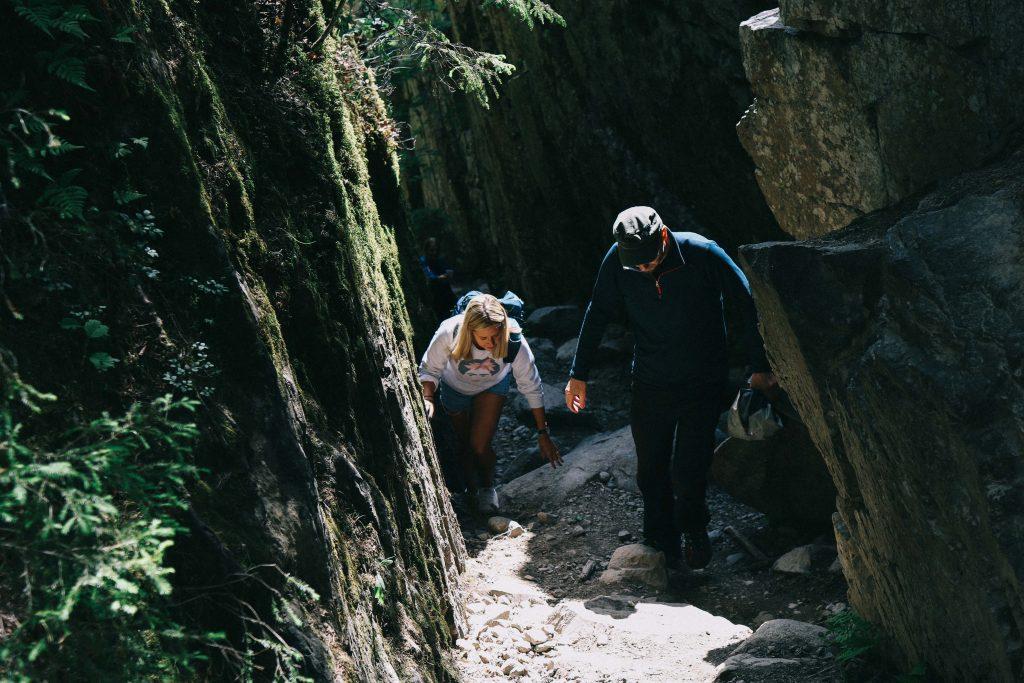 A girl climbing a steep rocky path in Helvetinjärvi National Park.