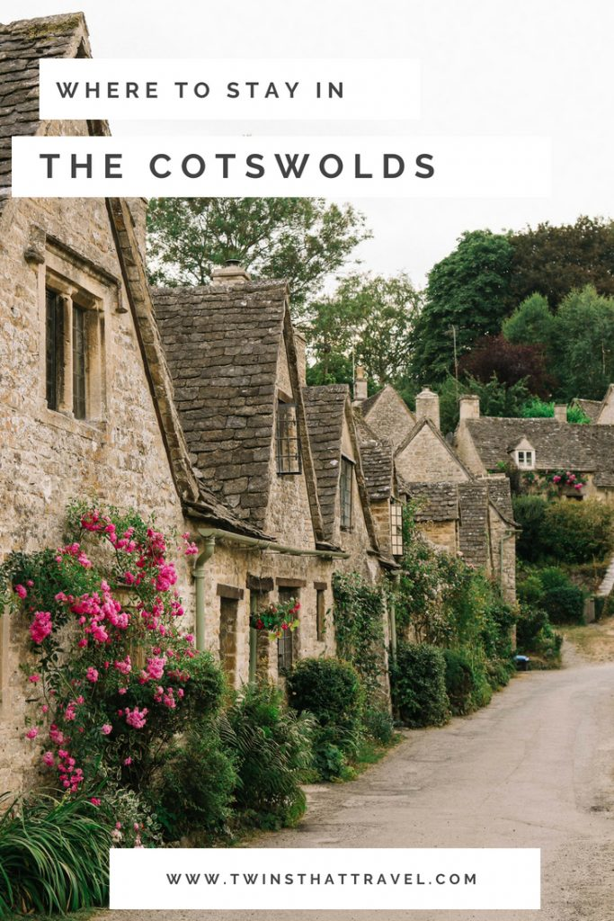 A photograph of cottages called Arlington Row in the village of Bibury, in the Cotswolds. They are surrounded by pink roses. Text overlay that reads: 'where to stay in the Cotswolds'. Written by Twins That Travel.